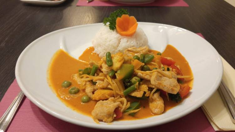 A decorative dish of chicken curry with jasmine rice on the side