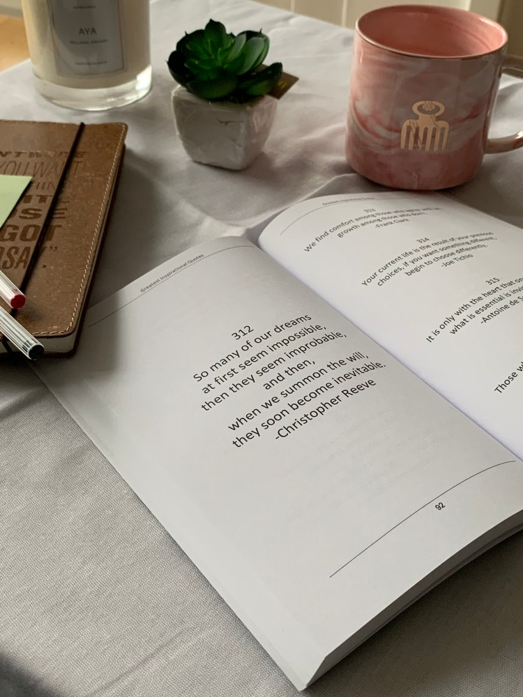 An open book with a quote with a mug, an artificial plant, and a candle in the background.