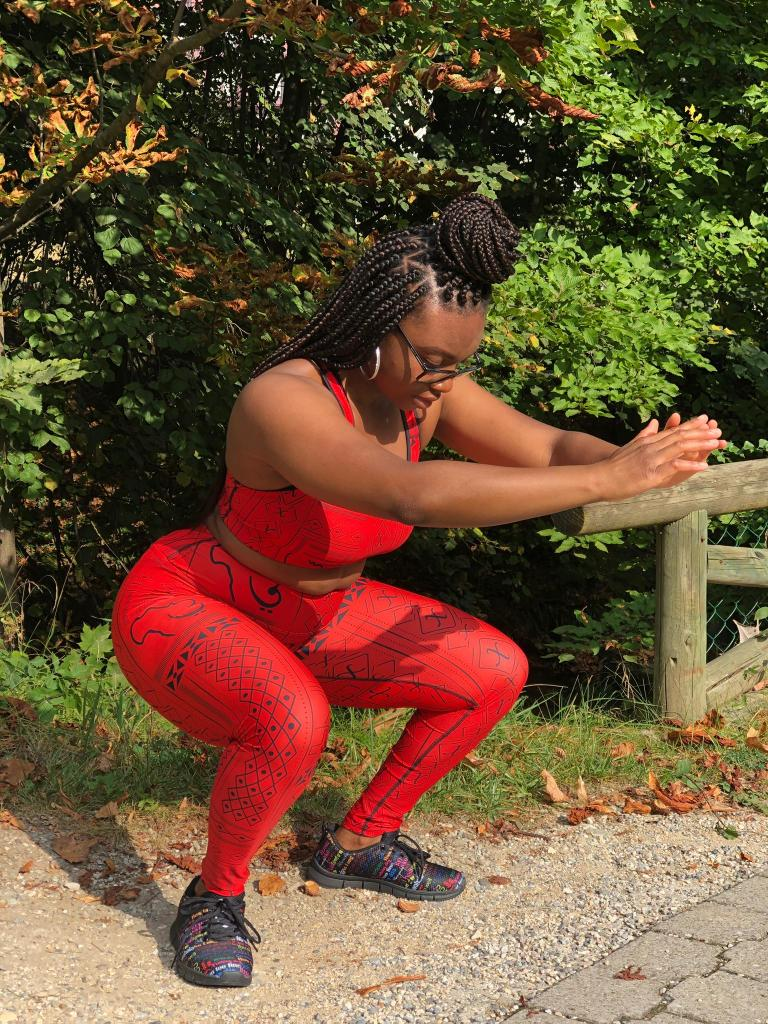 A Black woman with braids in a squat position wearing a red sports bra and leggings with African design in a park.